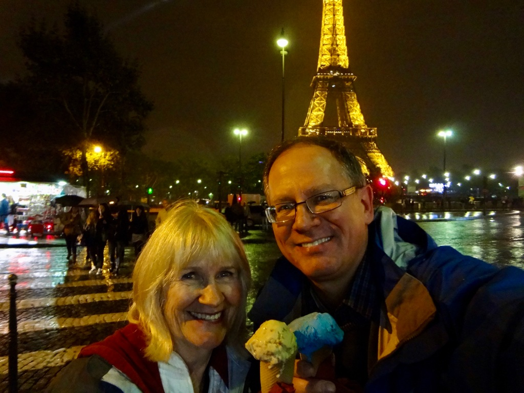 Photo of a woman and man eating ice cream on a rainy evening with the Eiffel Tower in the background.