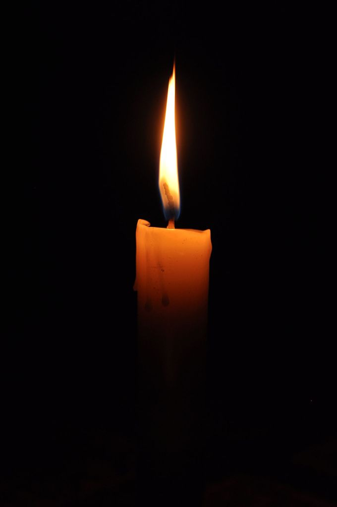 Photo of a lit candle against a black background.