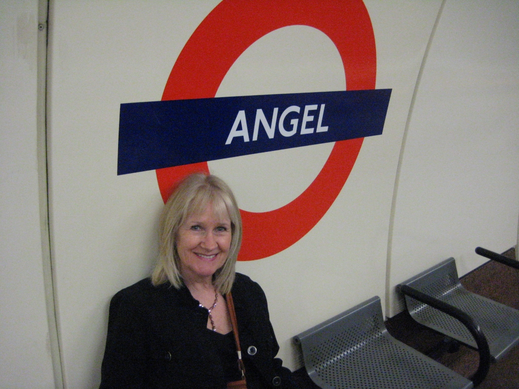 Photo of a woman sitting on a bench in a London Underground train station.