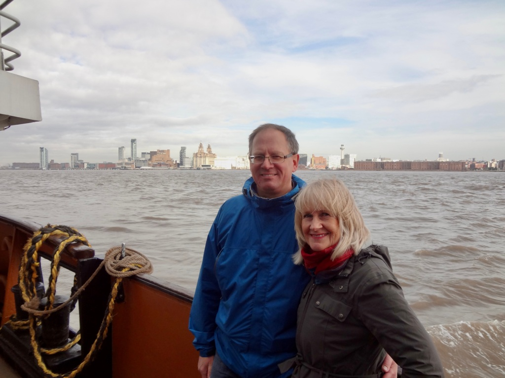 A man and woman on a boat, with the Liverpool, England cityscape in the background.
